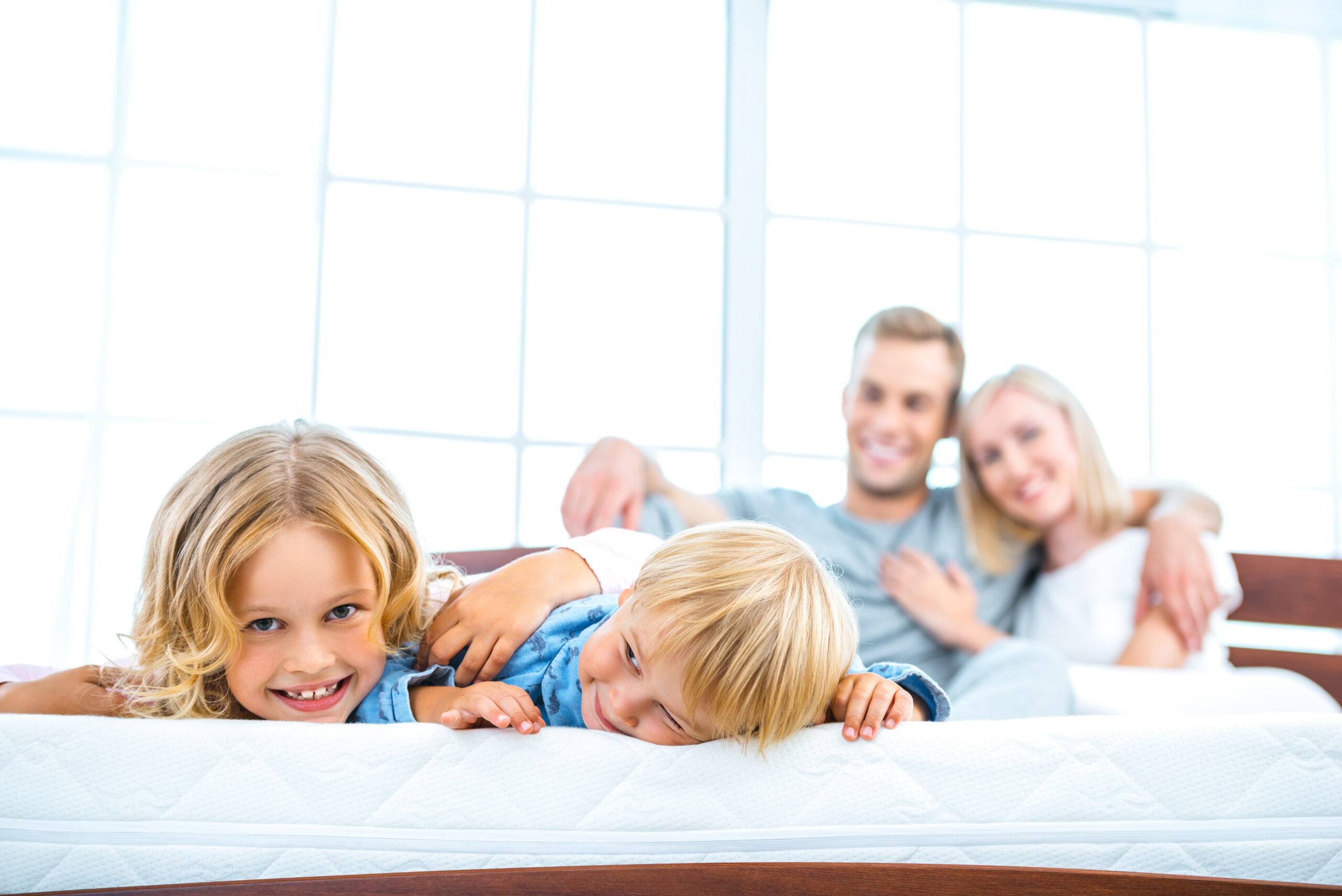 Image of Young family lying on white bed