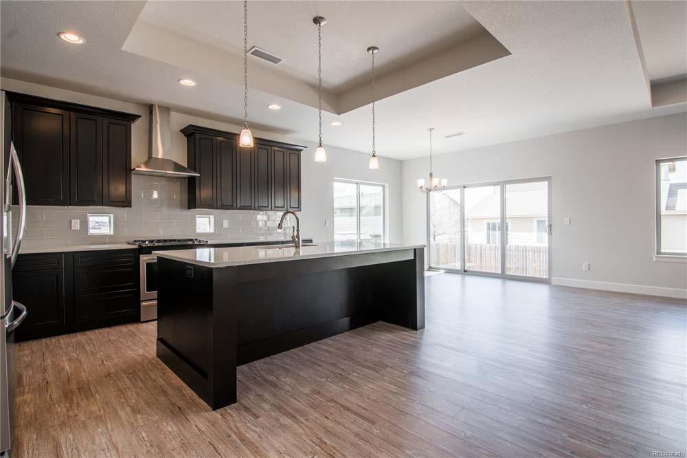kitchen with hardwood floors and modern lighting fixture
