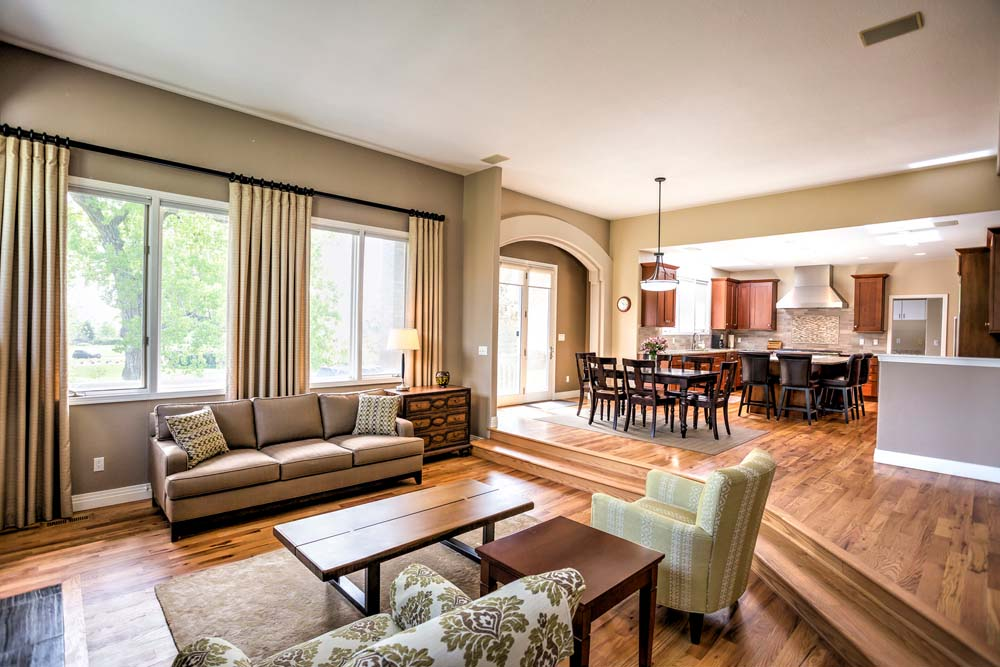 sunken living room with dining and kitchen in the background
