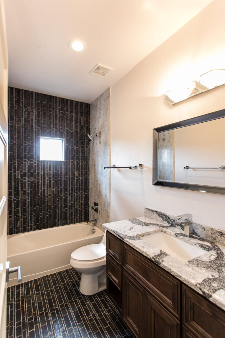 bathroom with granite countertops and black tiling