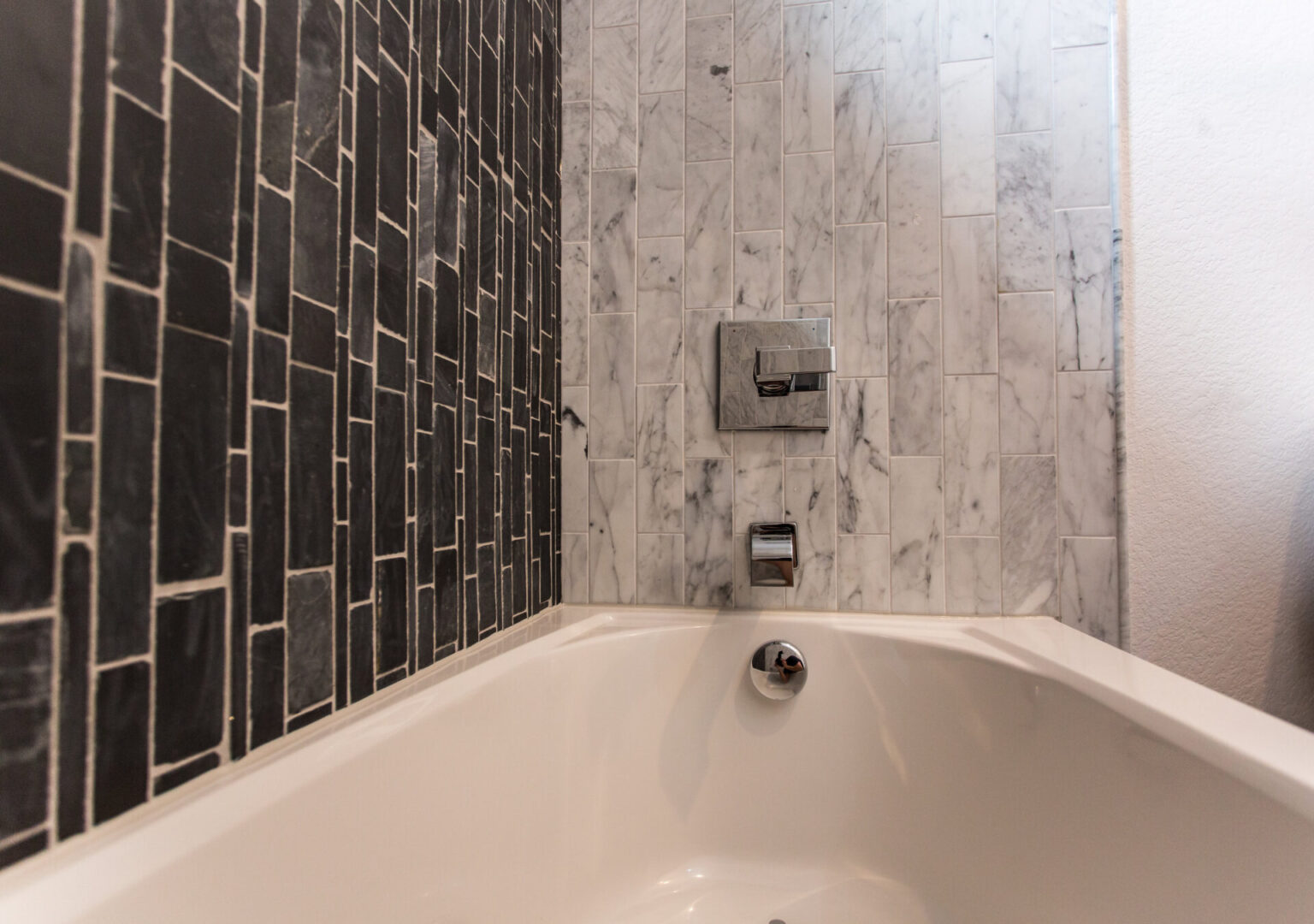 bathtub with marble and black tiles