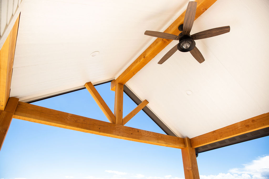 ceiling of a house with fan and brown wooden beams