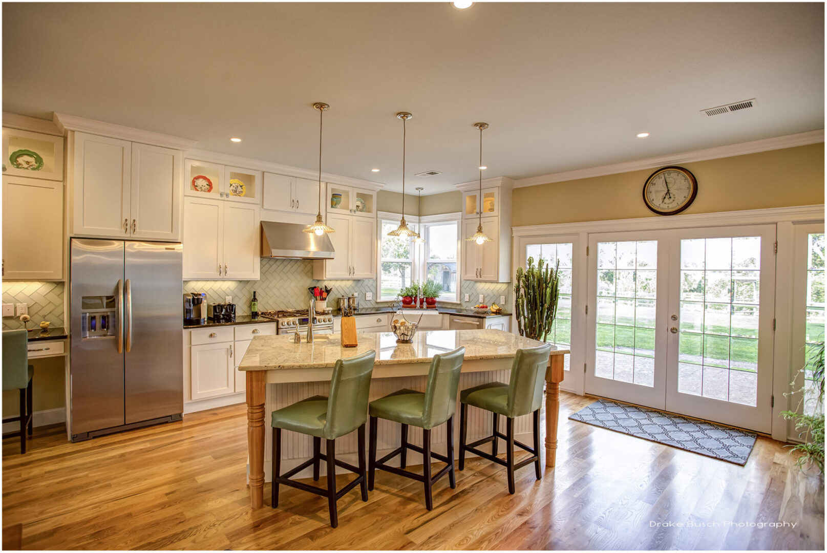 kitchen with marble island with seating with large windows and clock