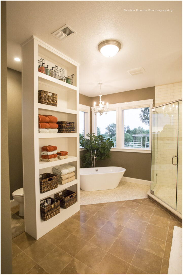 bathroom with tub and cabinet with towels