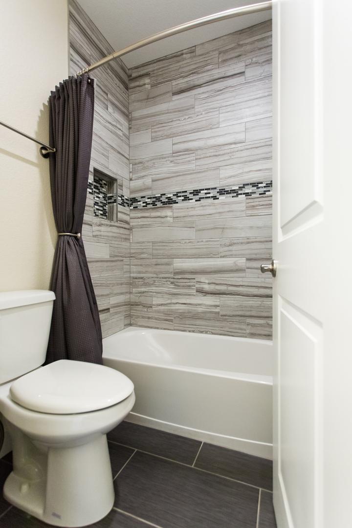 bathtub and toilet with wood-like tiles
