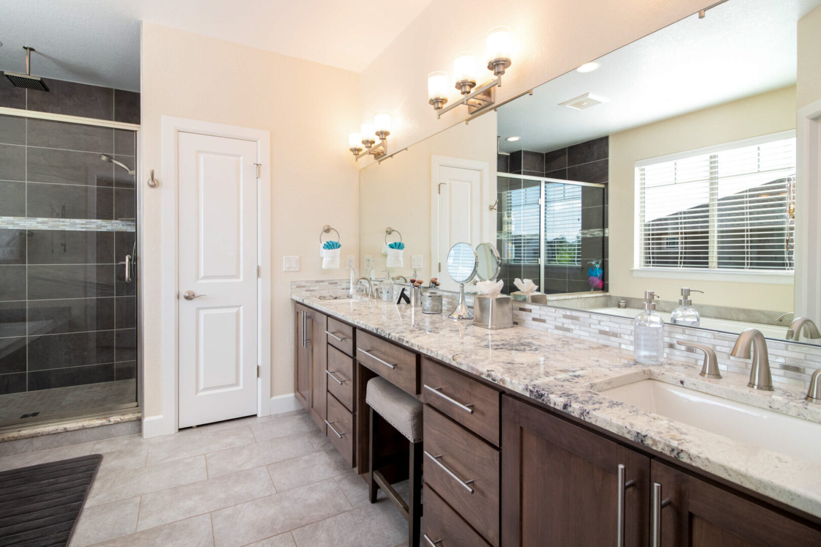 bathroom sink with granite countertop and warm lights