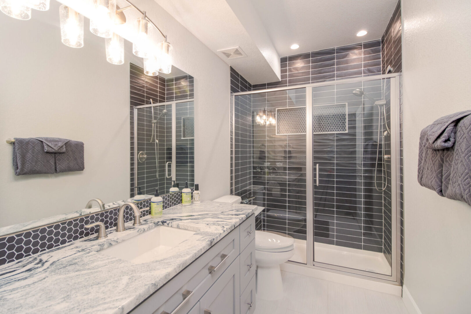 bathroom with marble sink and shower enclosure