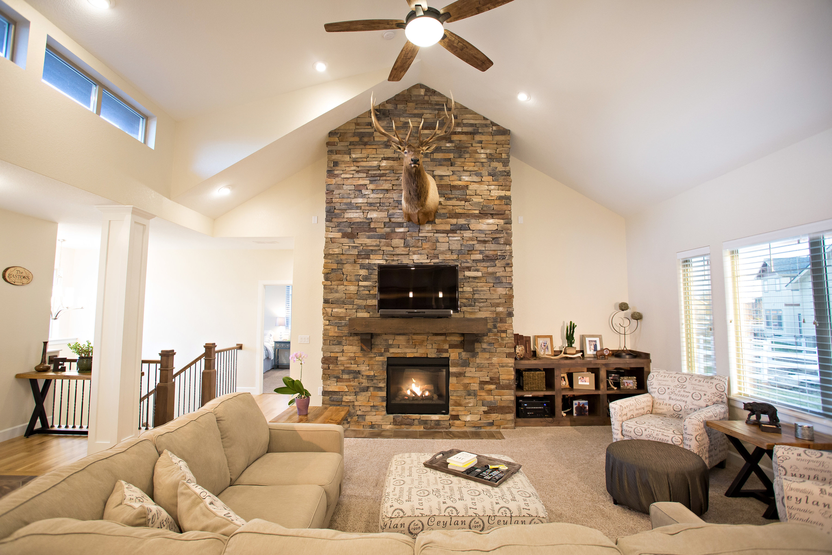 large living room with fireplace and stuffed deer head