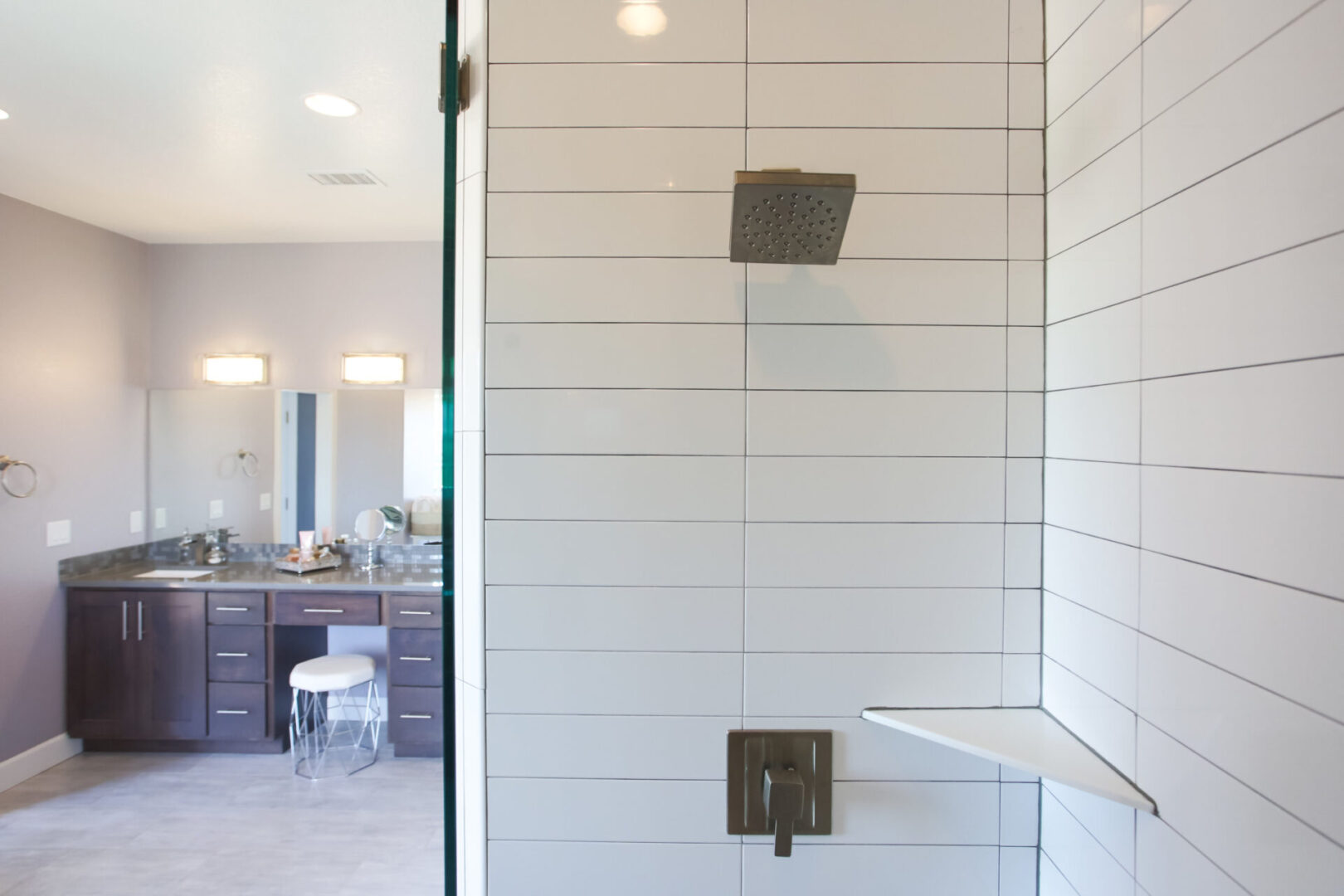 shower enclosure with rectangular white tiles with view of the bathroom sink