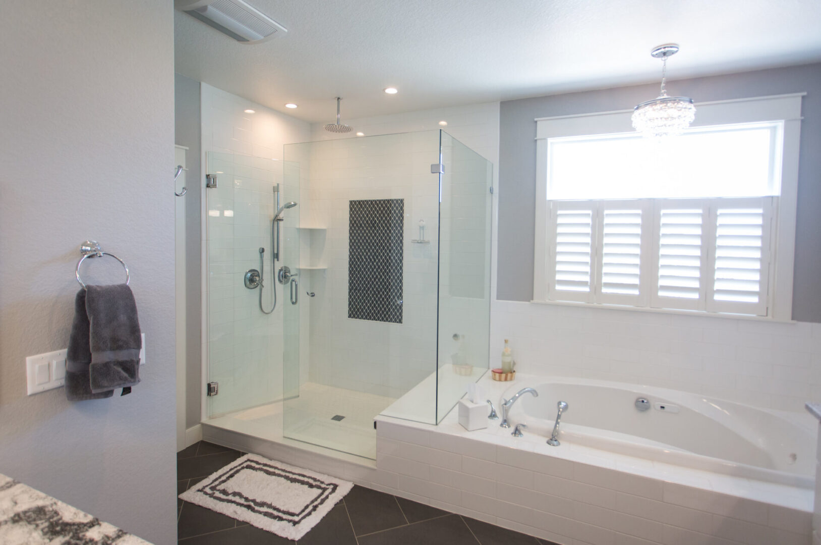 bathtub and shower enclosure with tiny chandelier