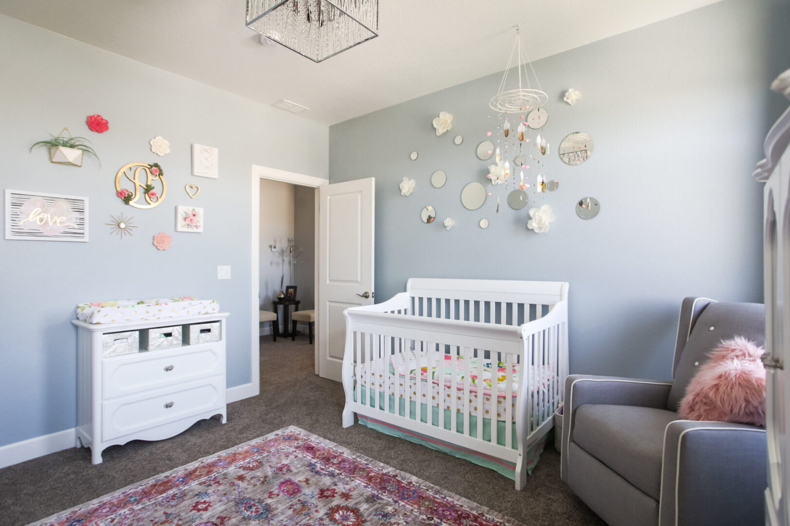 baby's room with crib and eggshell blue wallpaper