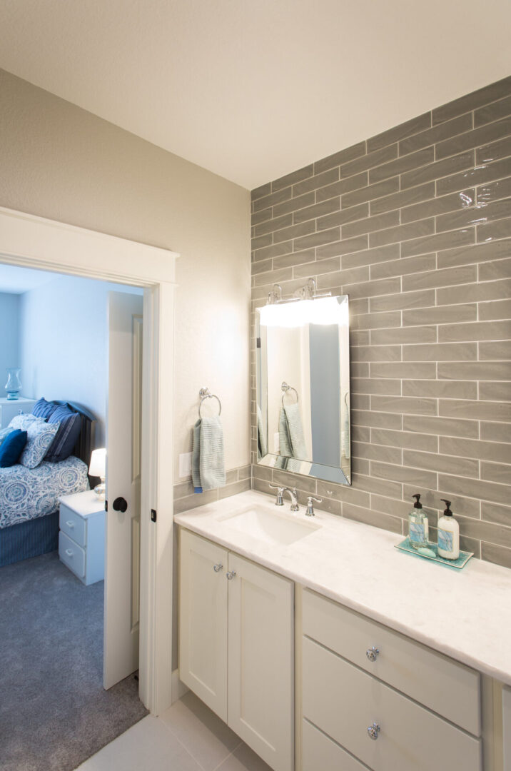 bathroom with brown tiles and view of a bedroom