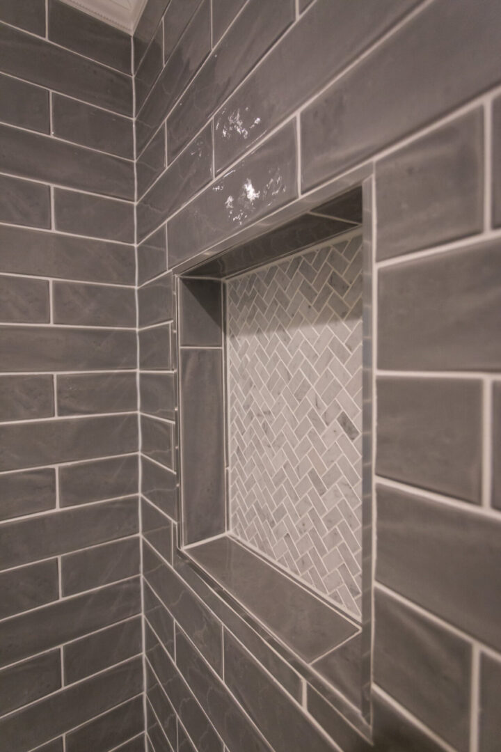 square hole in a bathroom wall with gray tiles