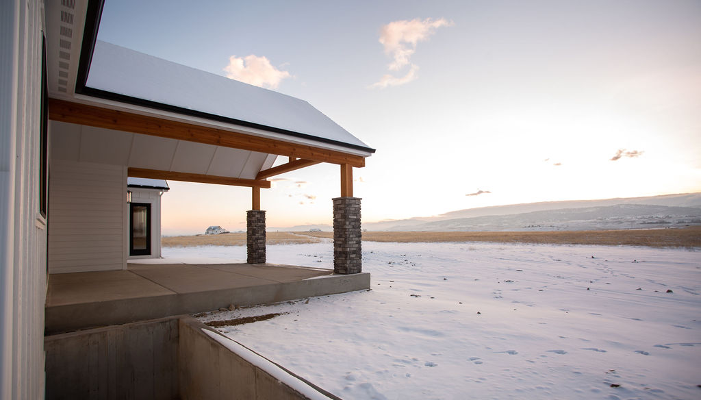 entrance of a house with snow overlooking gentle hills during sunrise