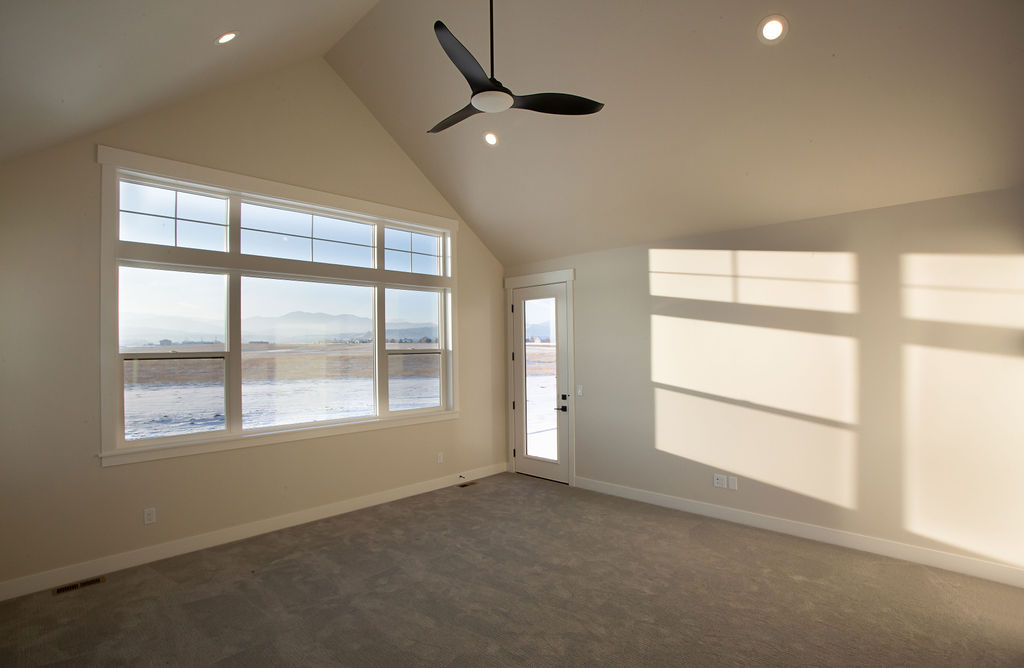 empty cream-themed room with ceiling fan
