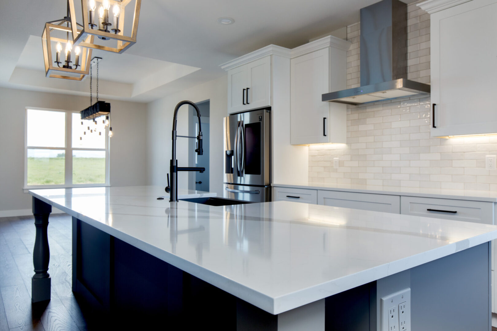 modern faucet and island of a white-themed kitchen