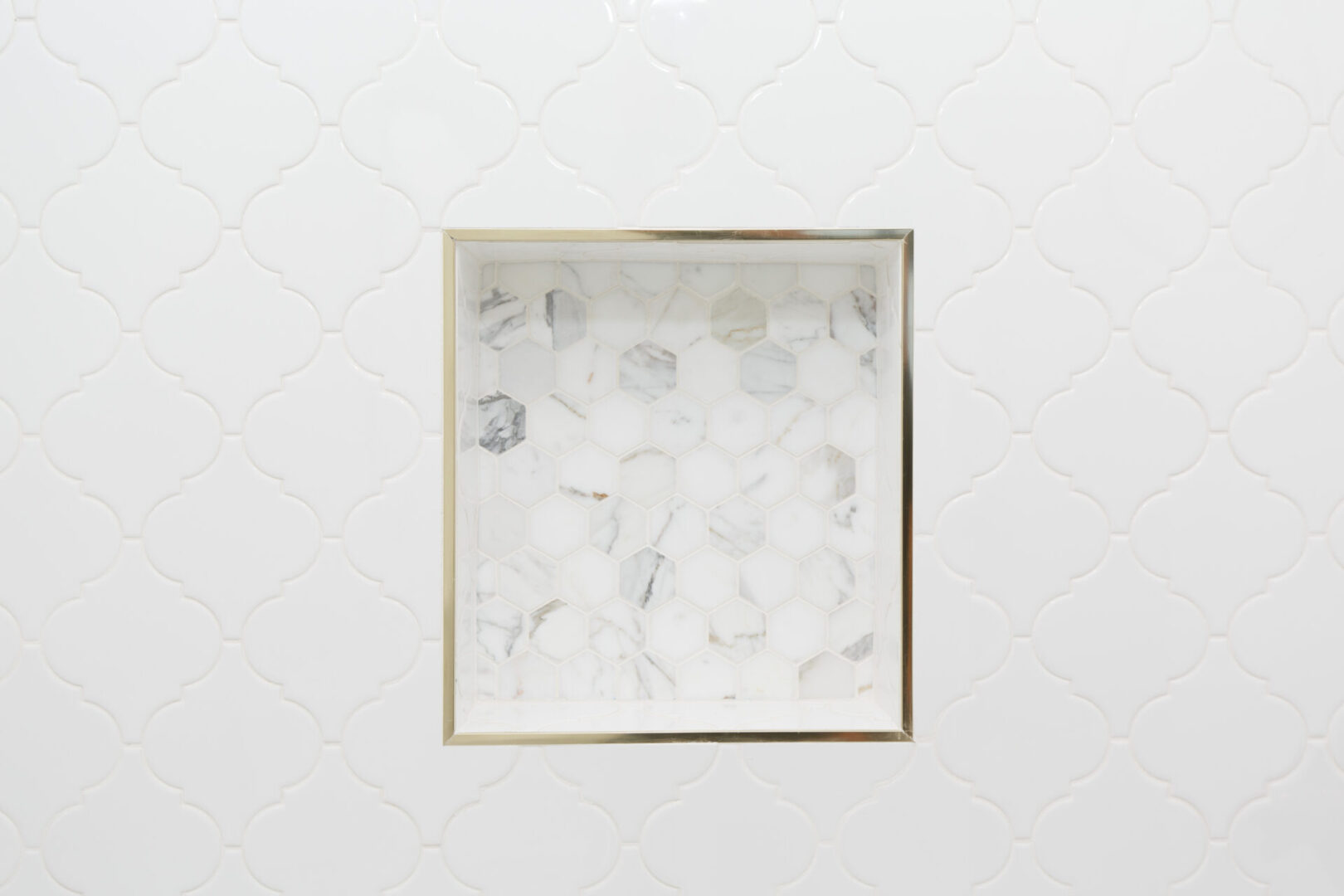 square hole in a bathroom wall with hexagonal tiles