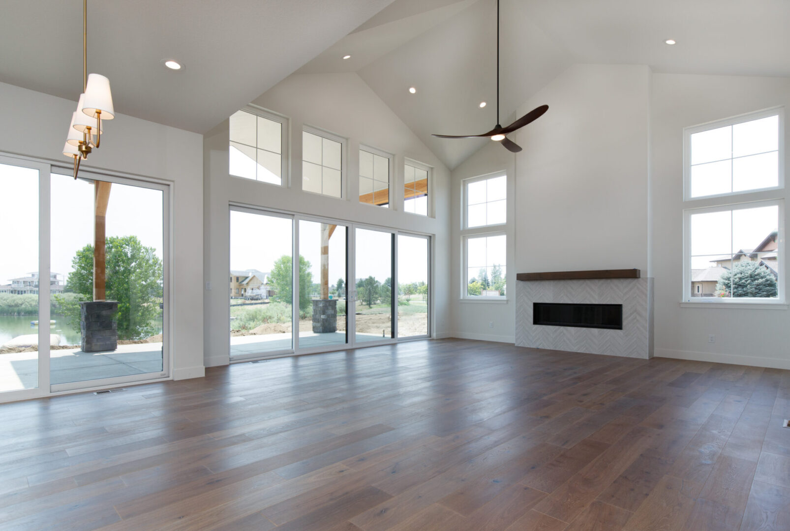 empty room with fireplace and ceiling fans