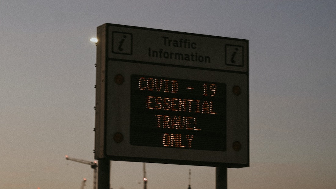 "A hoarding that says ""COVID-19 Essential Travel Only"""