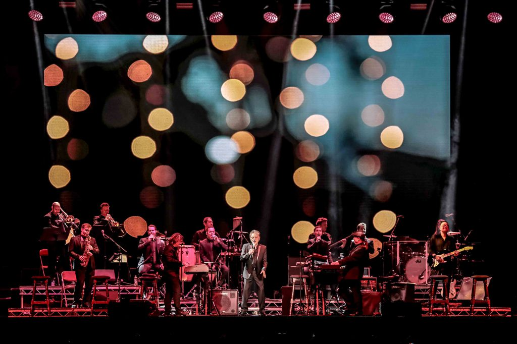 Frankie Valli with a full band onstage and bokeh background