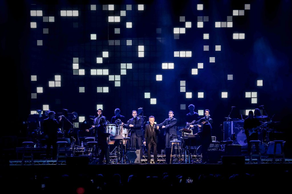 Frankie Valli in concert with a pixellated background