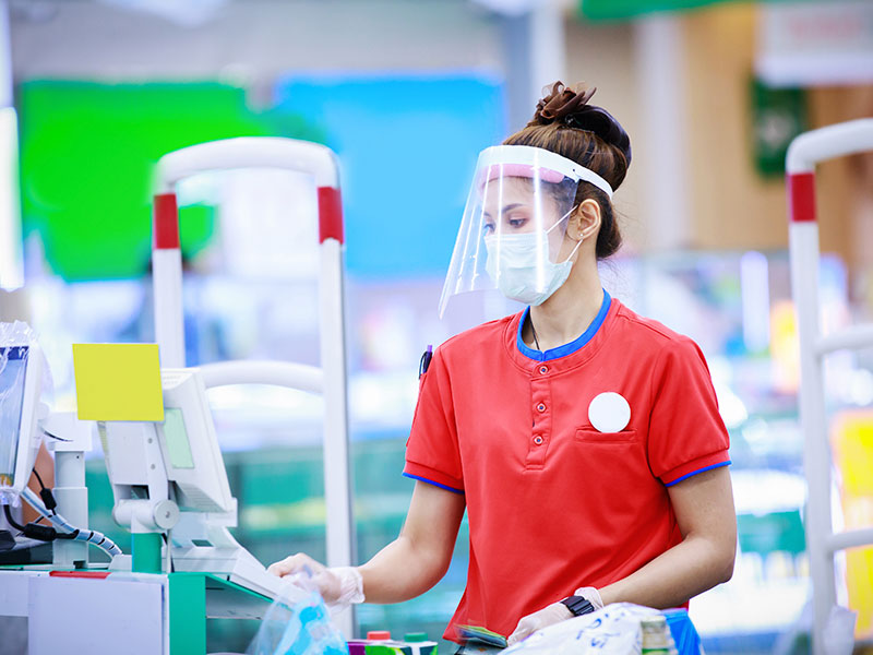 cashier with covid face shield and mask