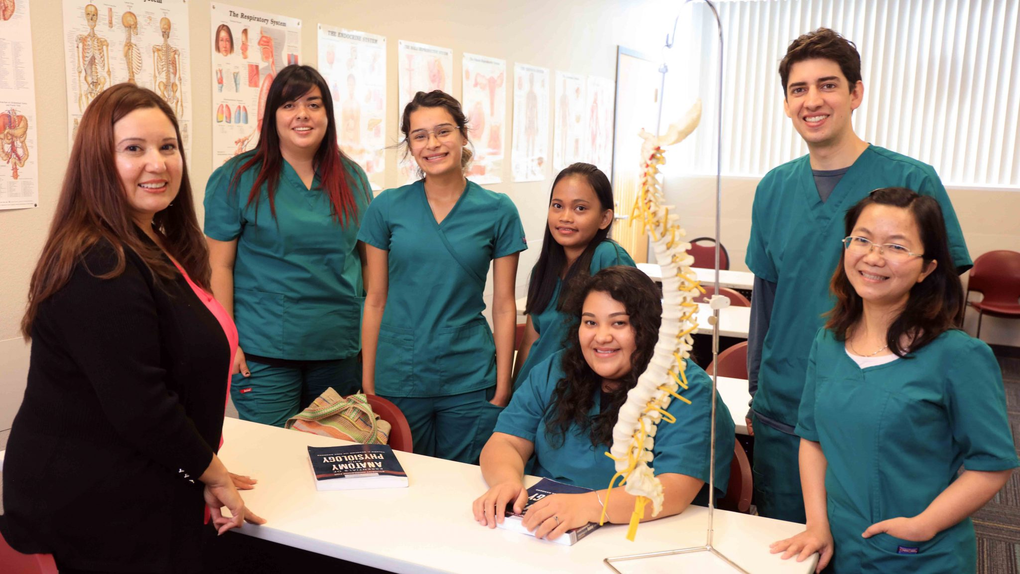 Five nursing students with an instructor in an anatomy classroom.