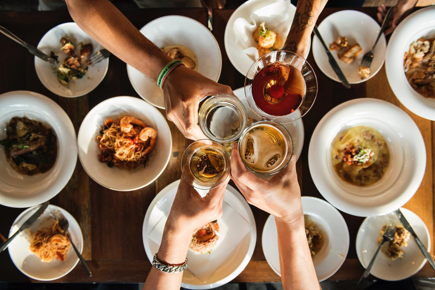 people toasting drinks with food