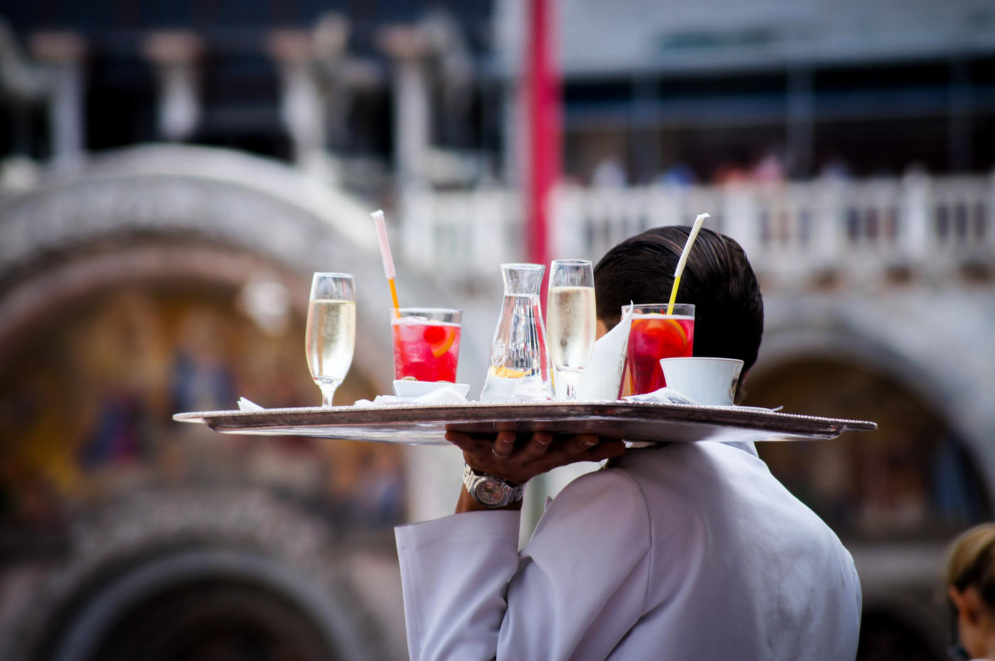 server bringing out drinks on a metal platter