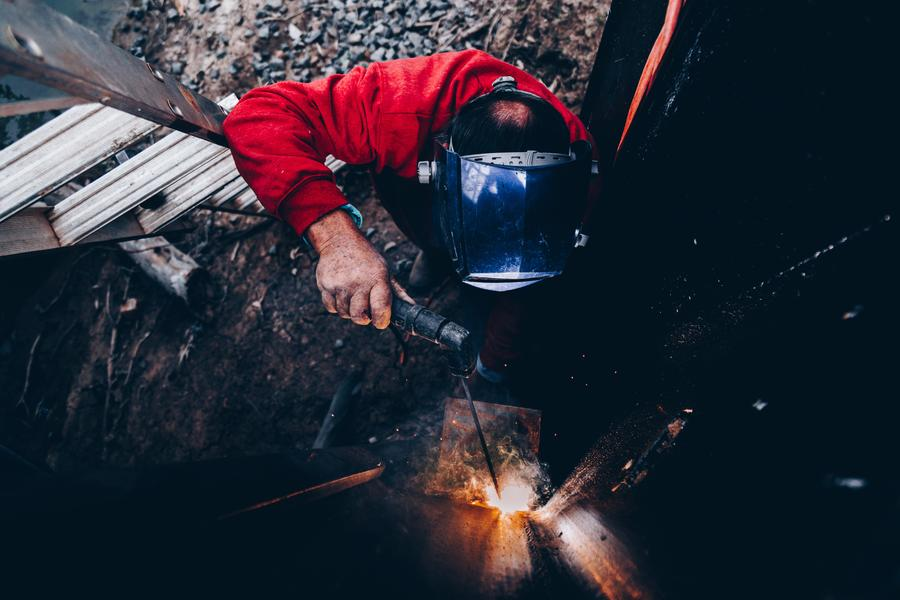 man welding a metal frame with sparks