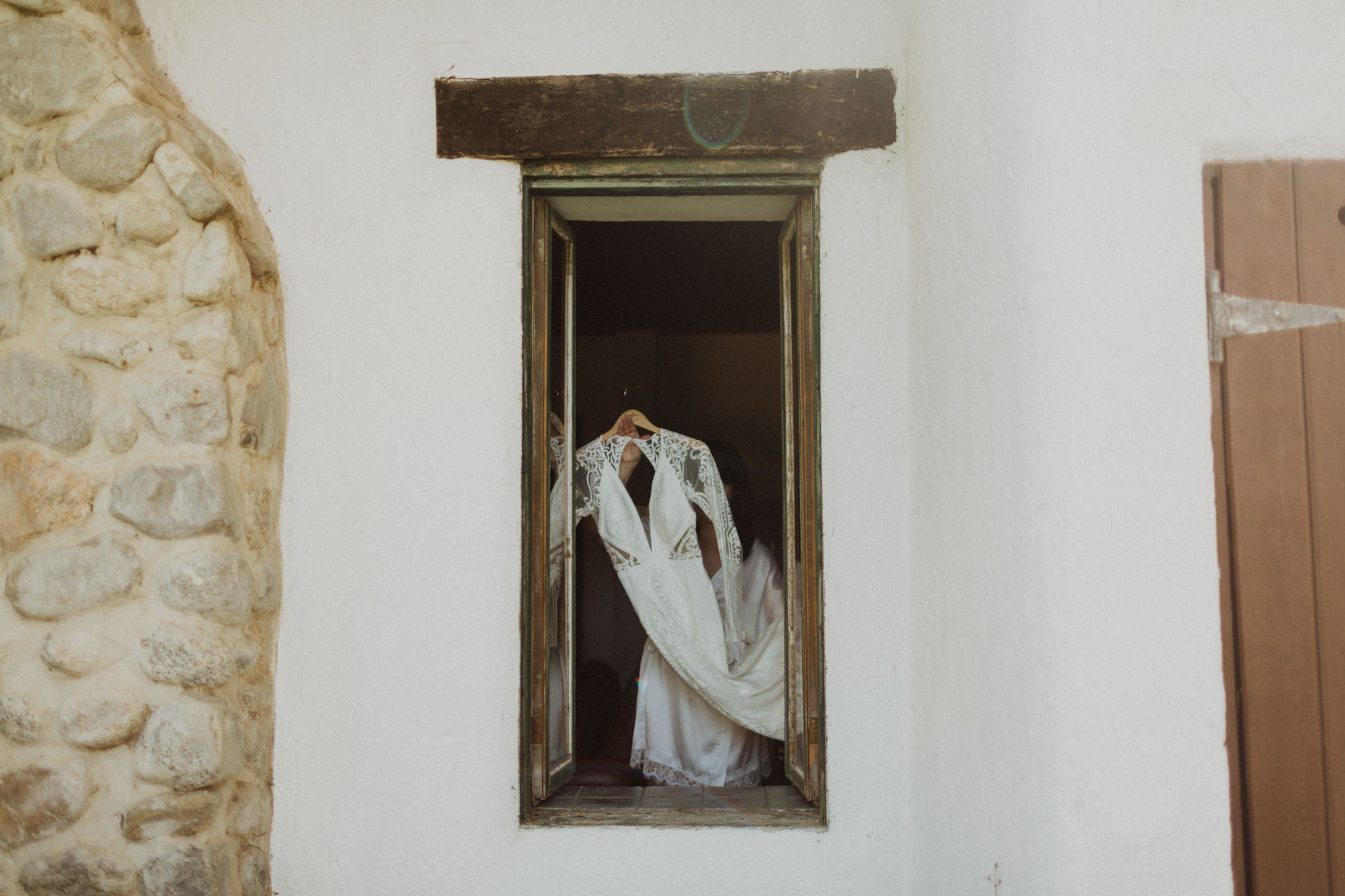 bride holding her dress in front of a window
