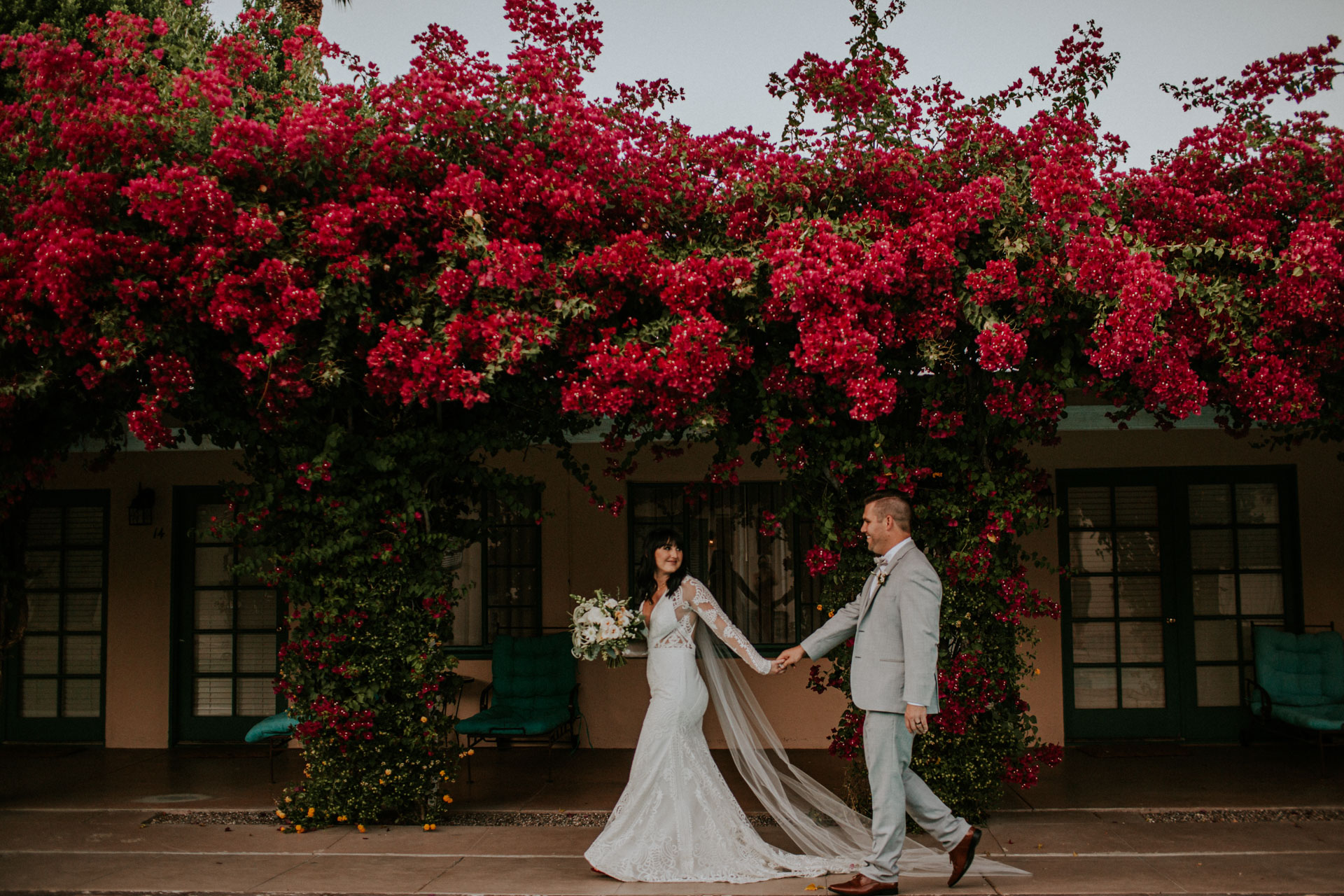 couple walking along wall of bright red bougainvillea