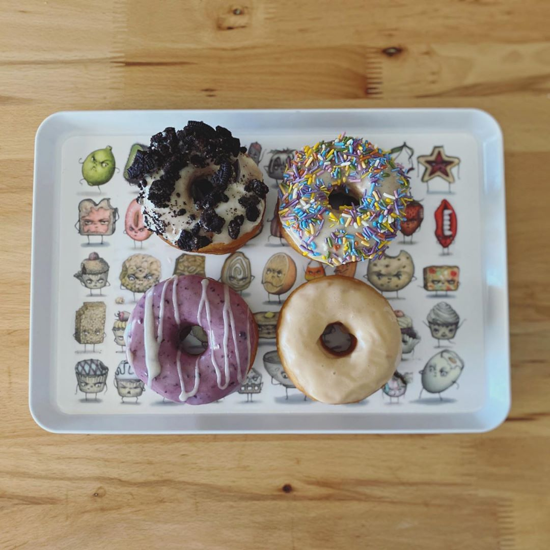 donuts on stray full of food characters sitting on light wood table