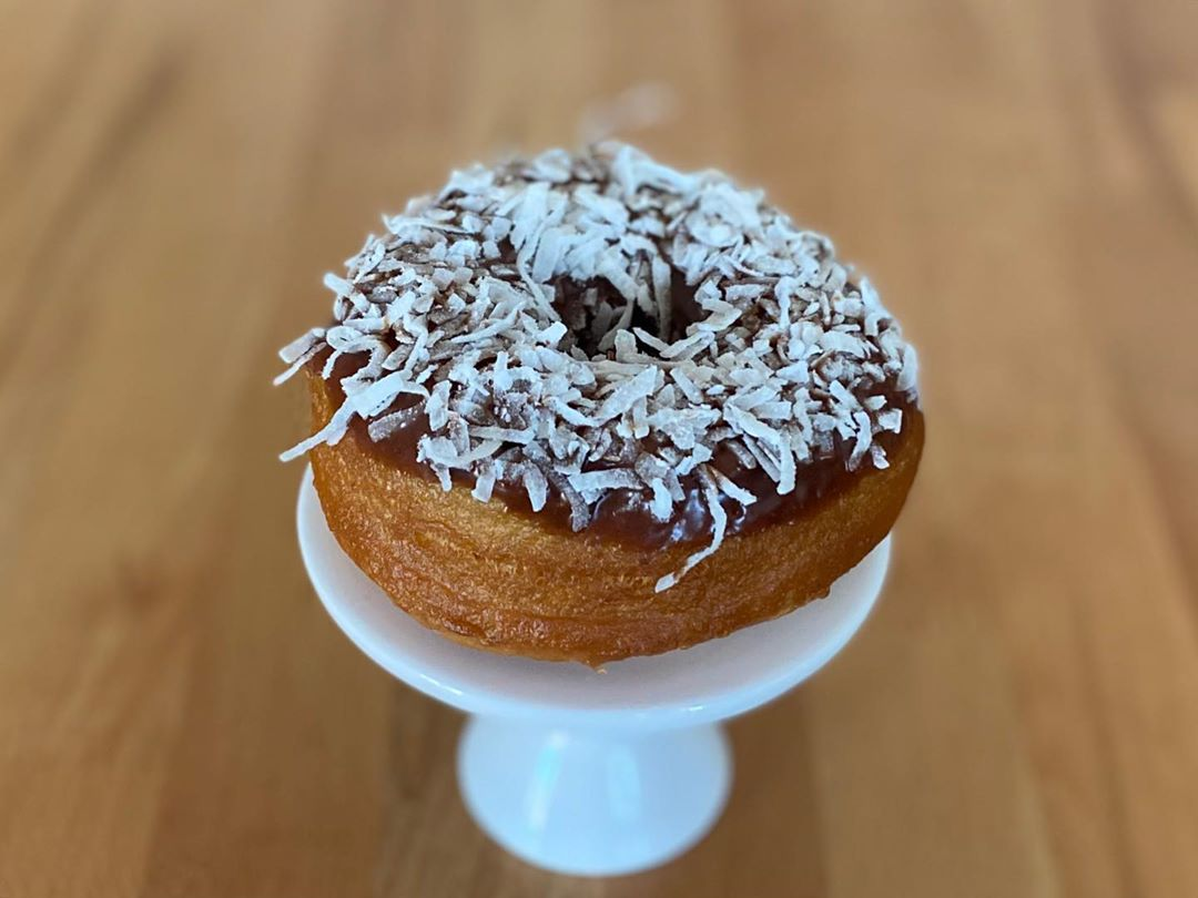 Coconu-tural Born Chocolate donut on white pedestal stand