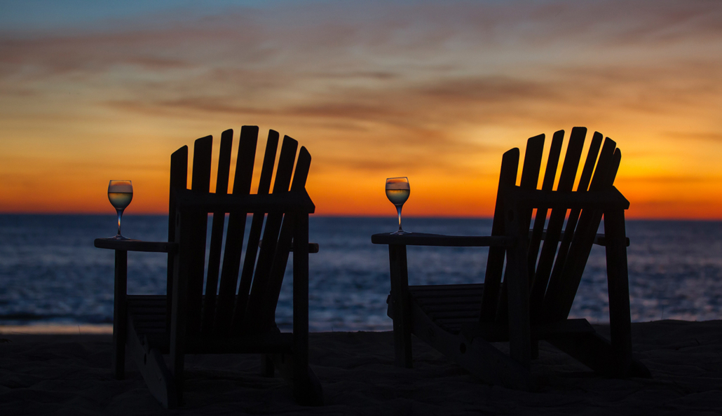 Two Adirondack Chairs At Shore
