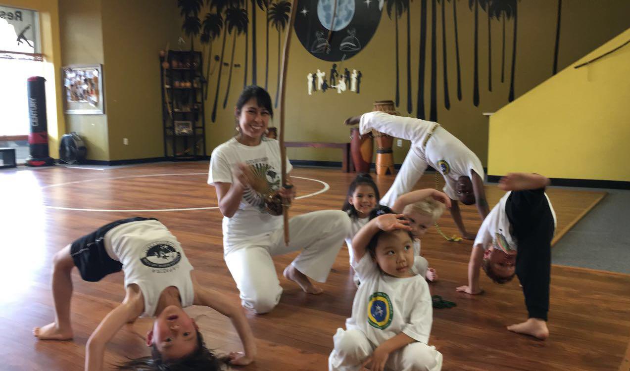 Kids pose in capoeira class.