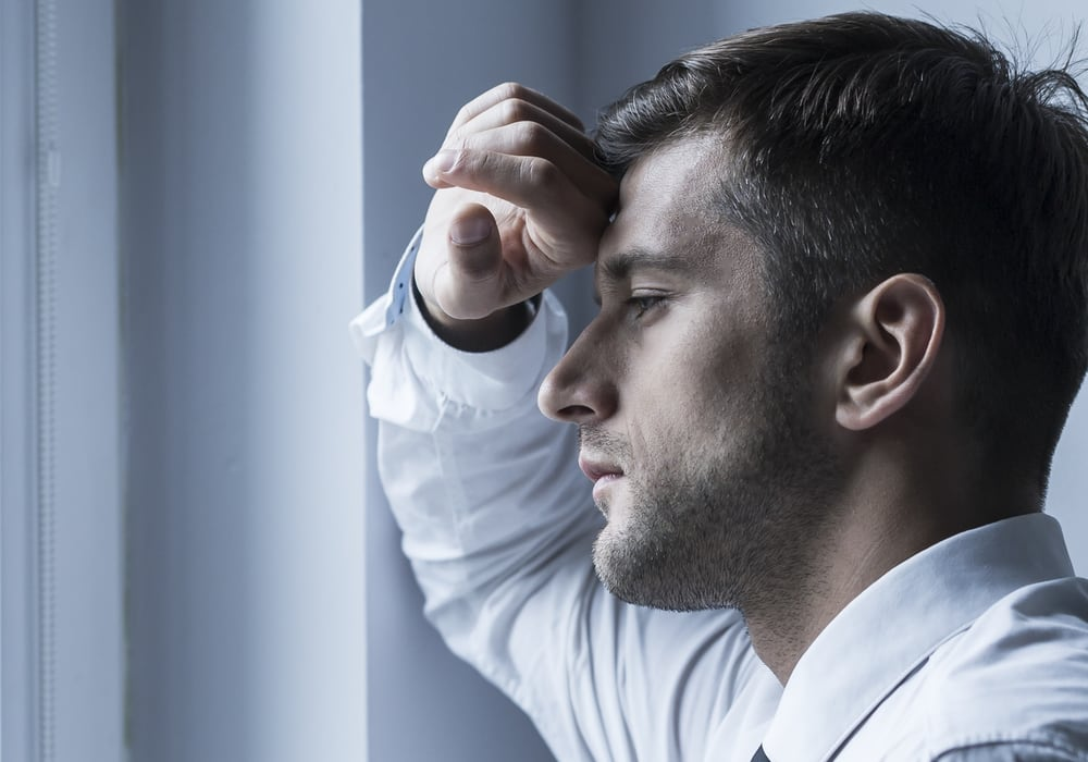 anxious man looking out window