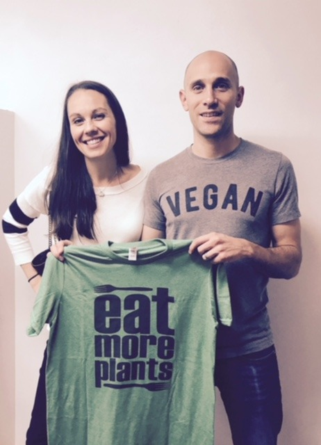 Man and women holding eat more plants shirt