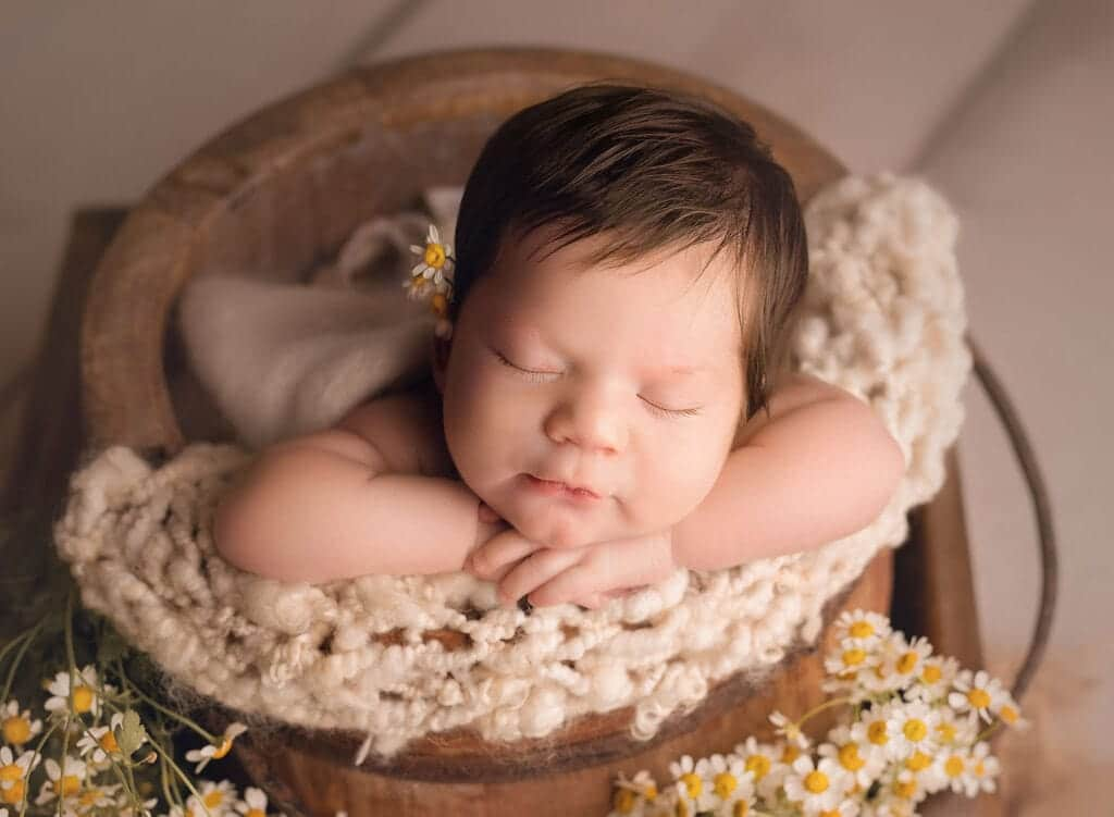newborn girl with flowers in her hair