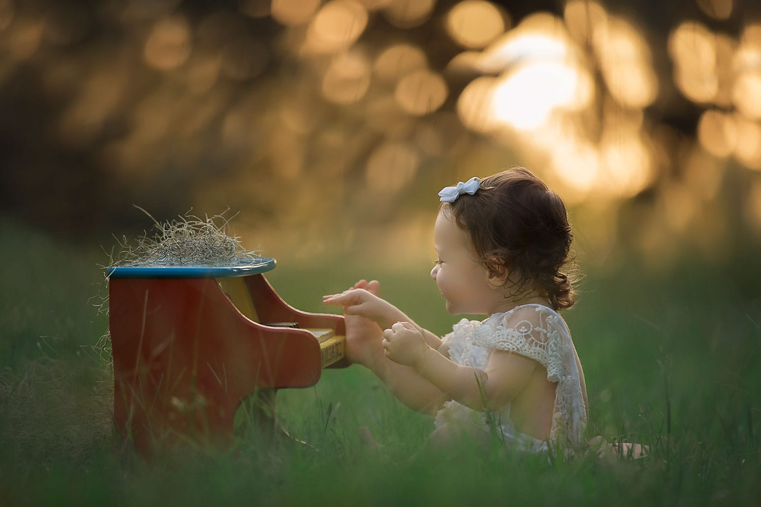 Beautiful baby girl in lace romper with toy piano by Annie Whitaker Photography