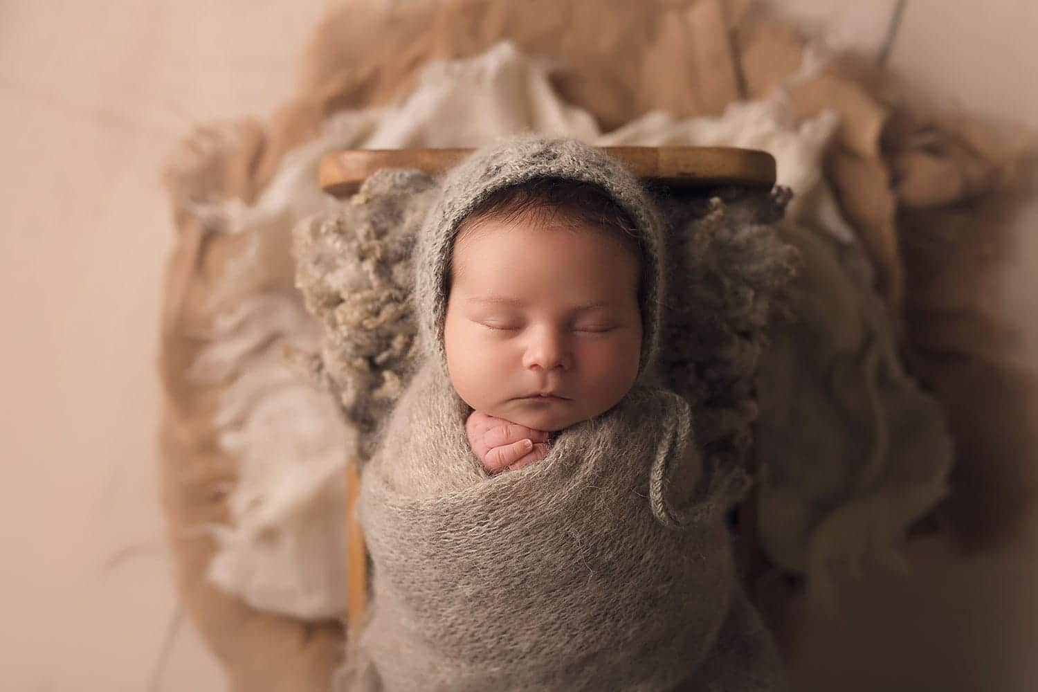 Newborn boy all snuggled in grey wrap and bonnet by Annie Whitaker Photography