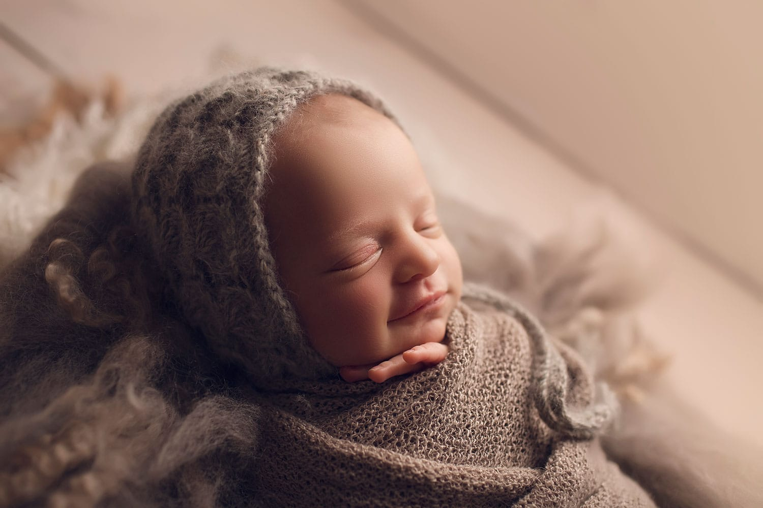 Baby girl in grey bonnet smiling by Annie Whitaker Photgraphy