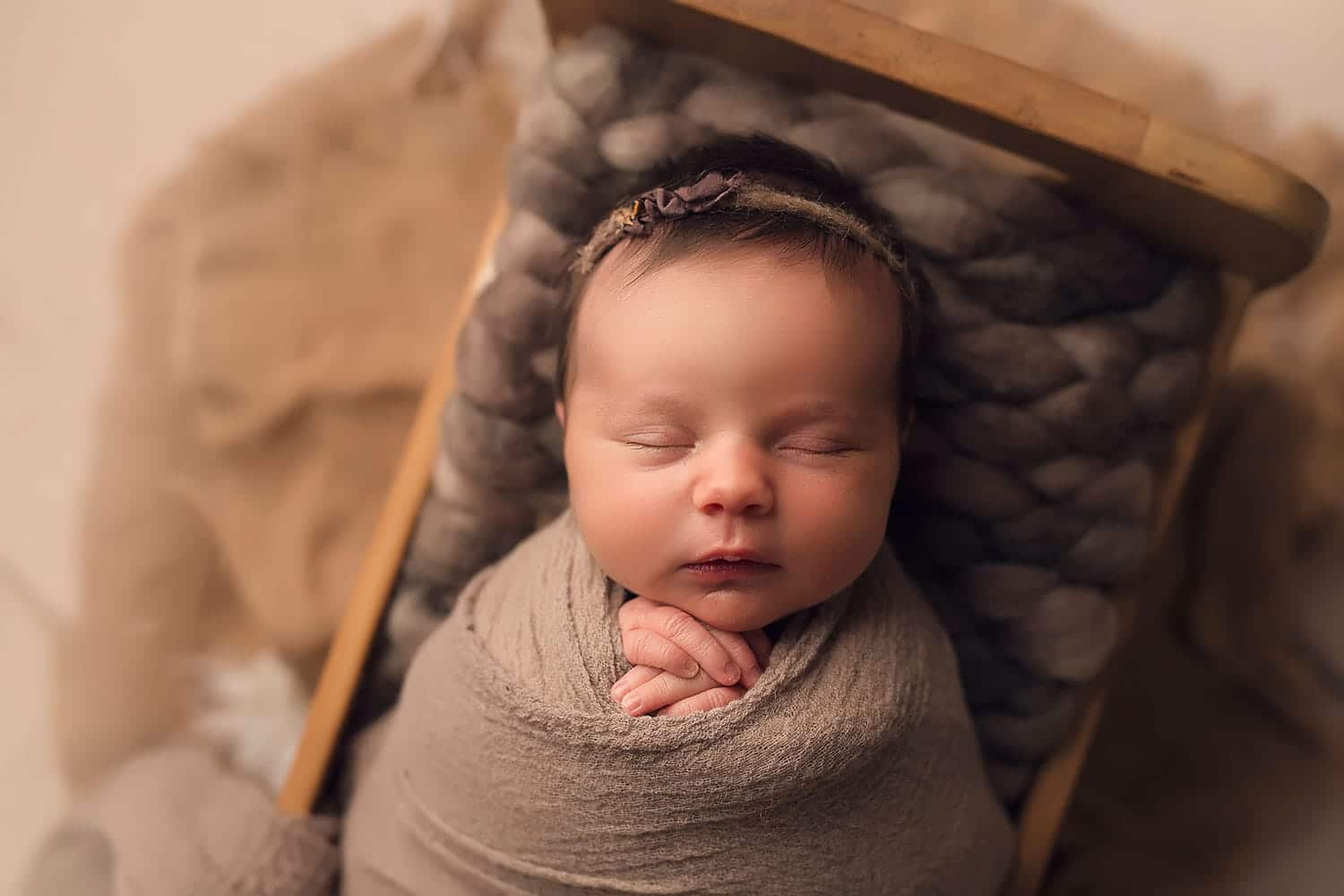 baby girl on brown bed by Annie Whitaker Photography