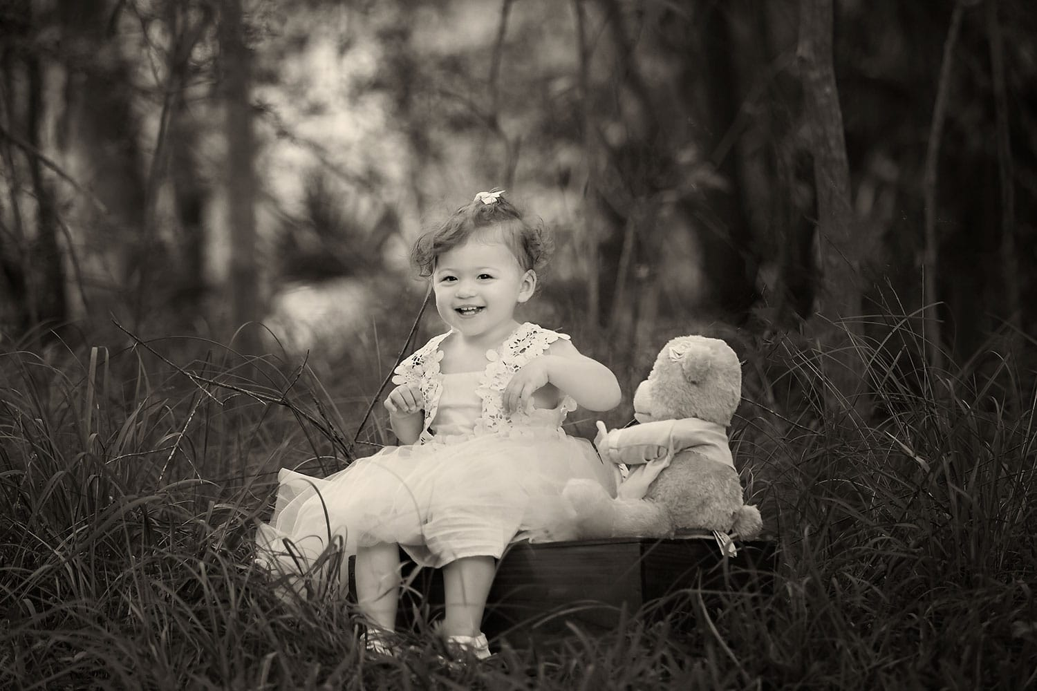 Smiling baby girl with teddy bear by Annie Whitaker Photography