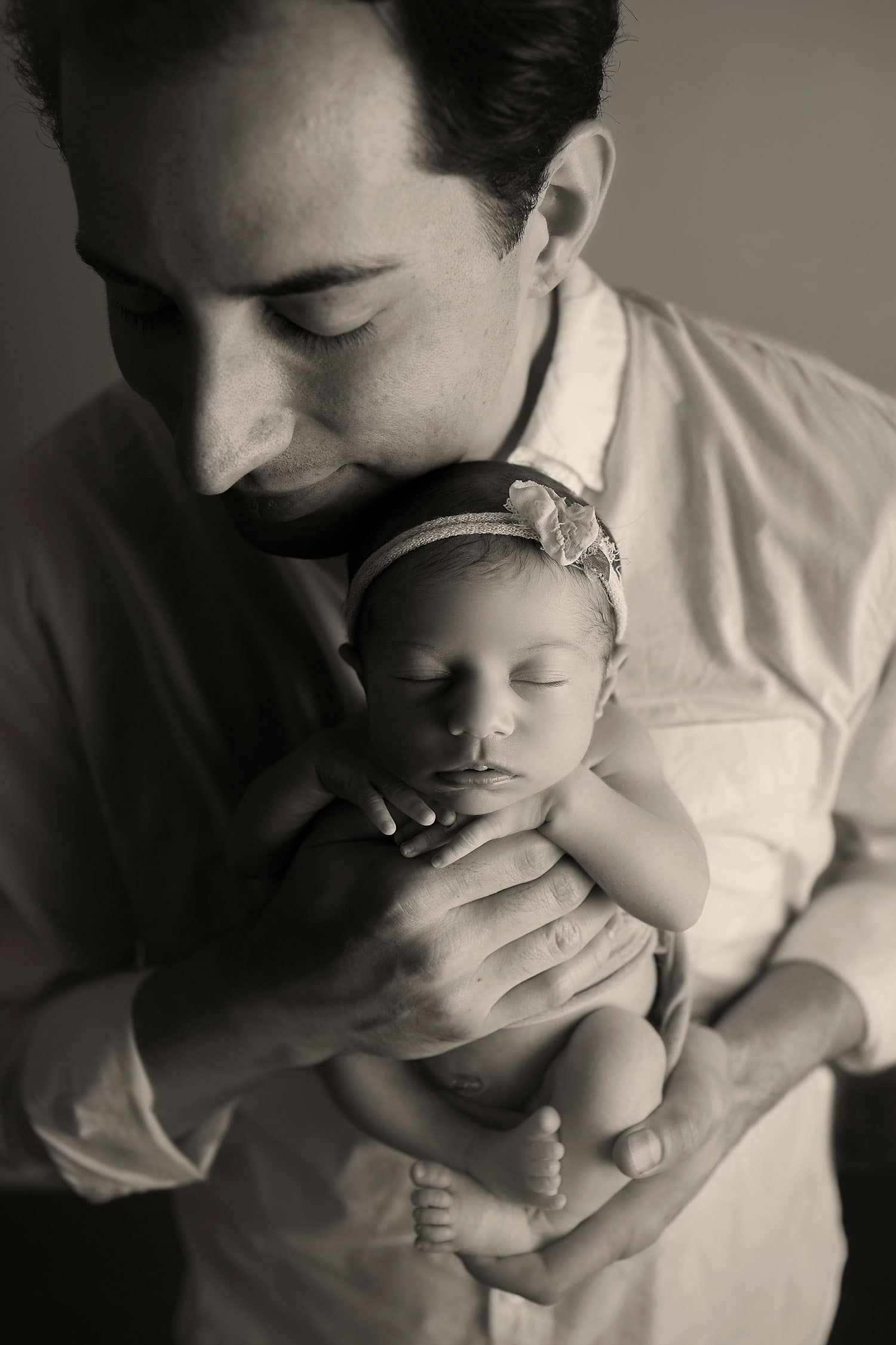 Dad holding newborn by Annie Whitaker Photography