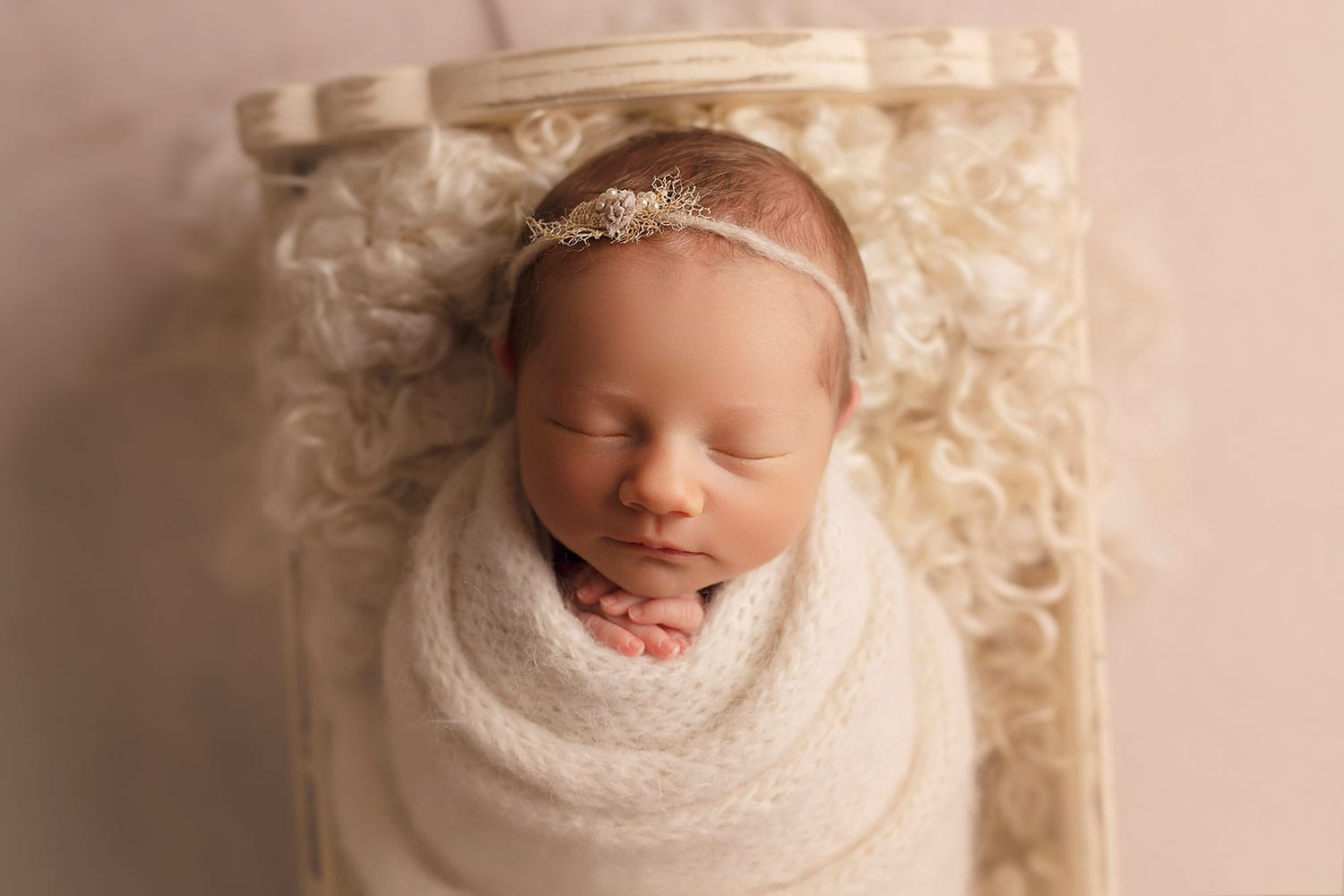 Baby girl in tiny white bed by Annie Whitaker Photography