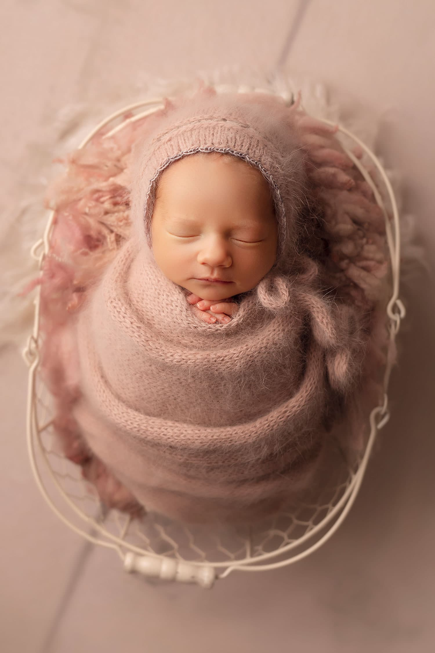 newborn baby in basket with pink cwtchicoo fluff by Annie Whitaker Photography