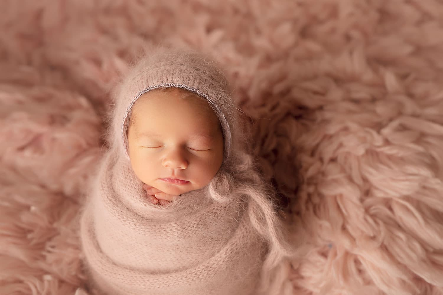 Newborn girl on pink flokati by Annie Whitaker Photography