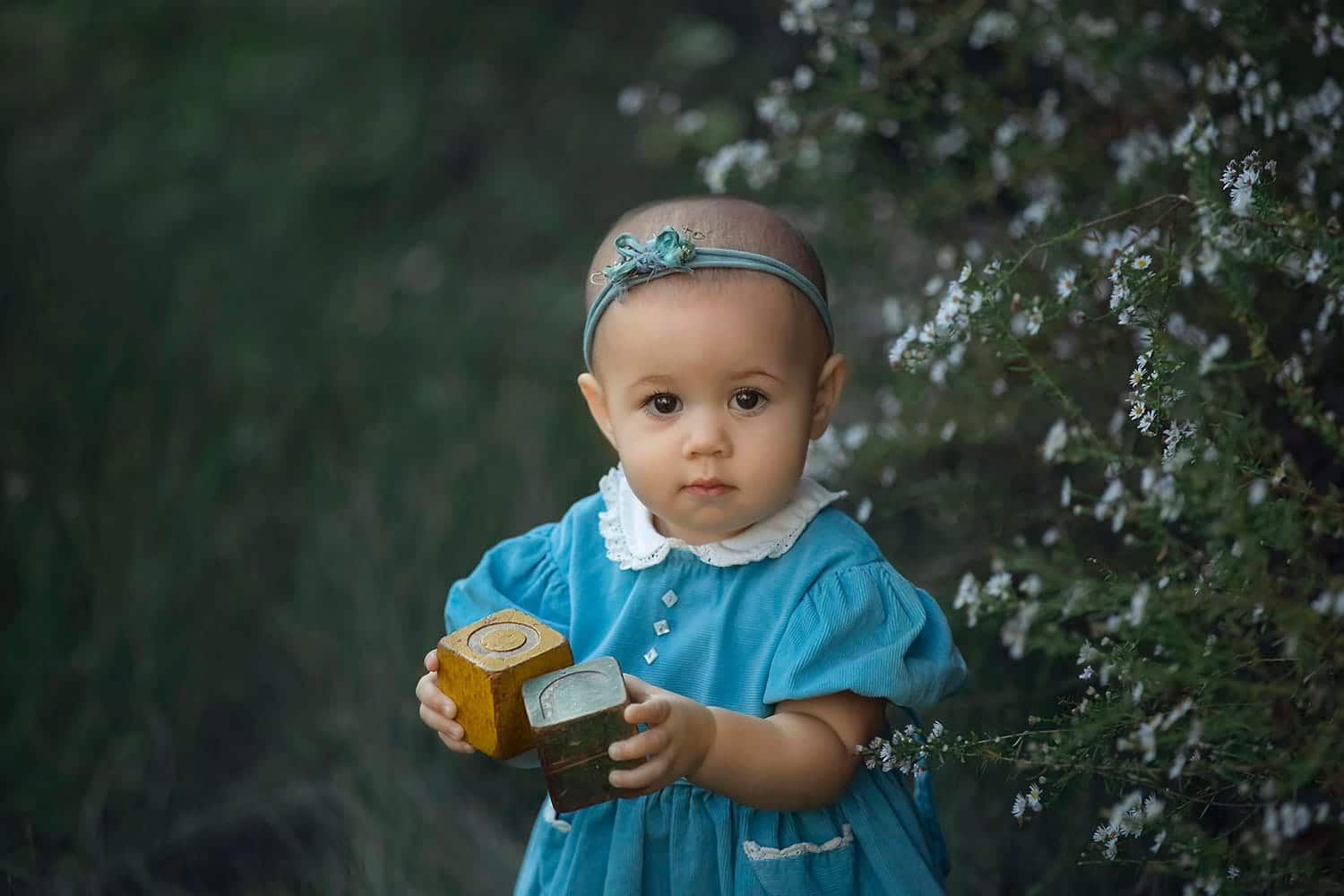 Stunning one year old girl in vintage dress holding blocks by Annie Whitaker Photography