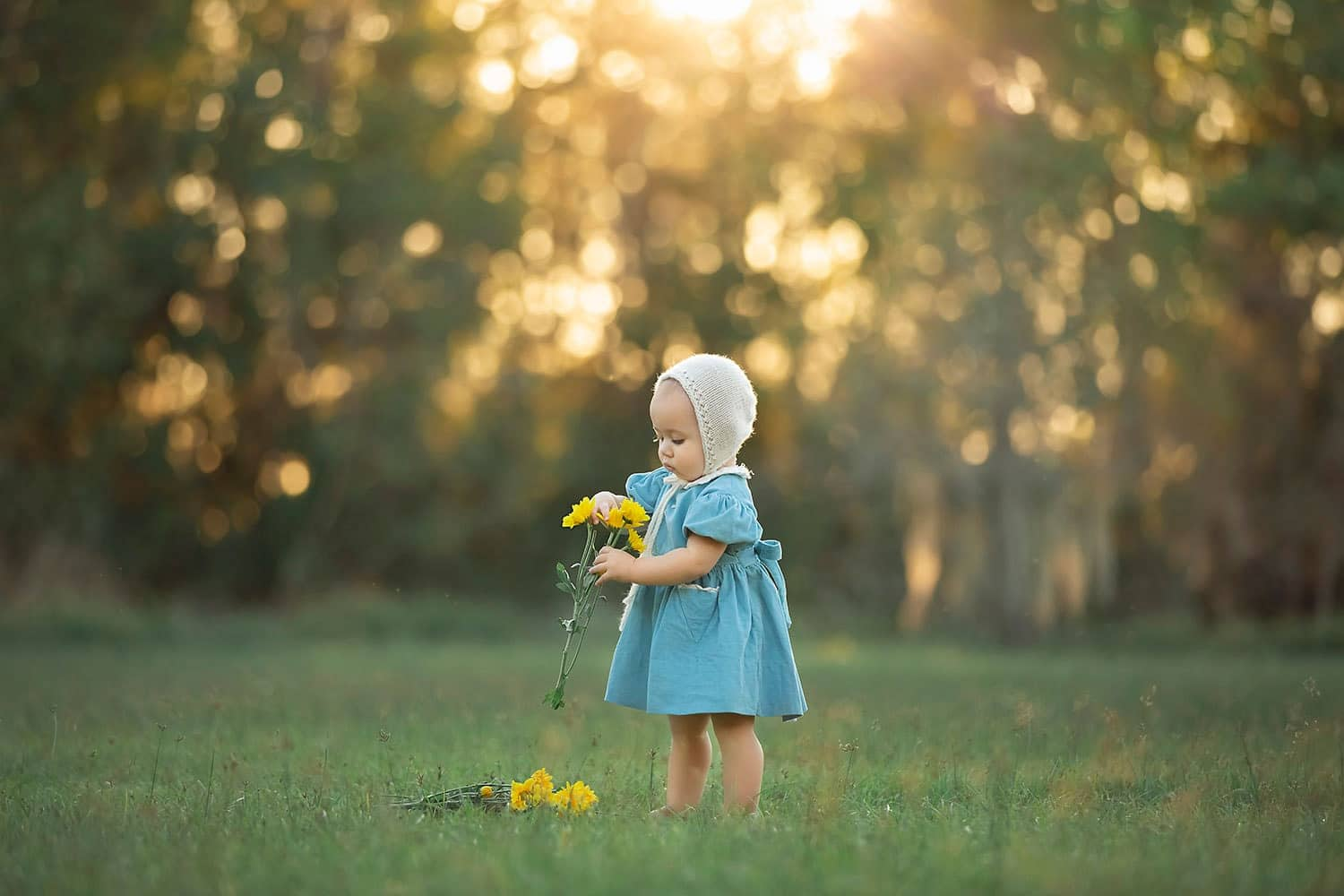 Baby girl at sunset holding yellow flowers by Annie Whitaker Photography